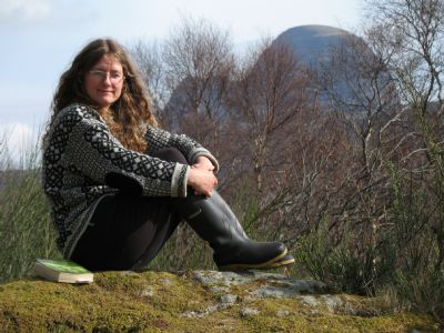 Mandy Haggith outside with a book - Suilven close - Photo from Mandy's website