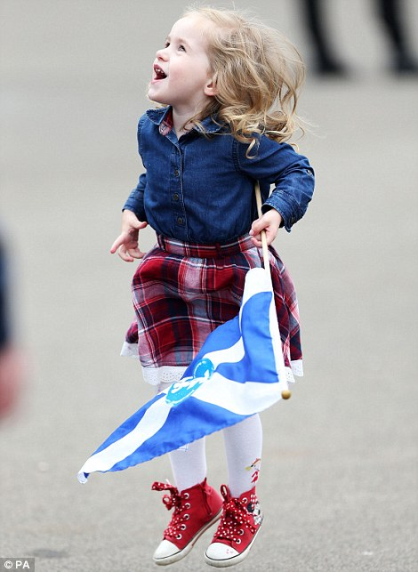 A young girl carrying the Scottish flag