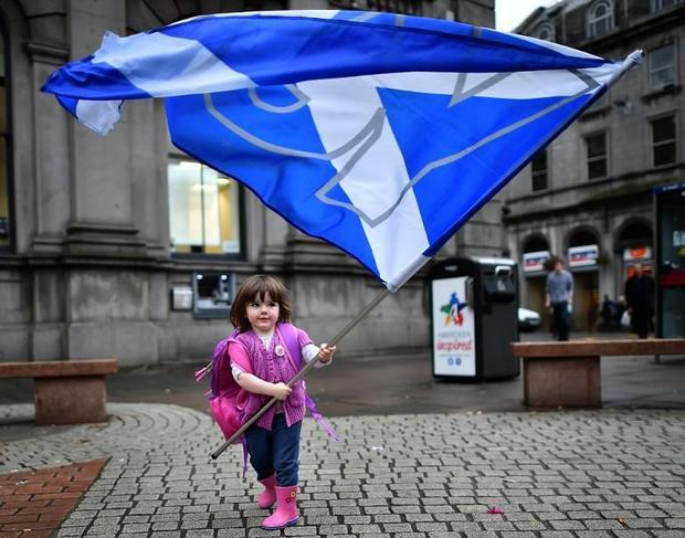 Aberdeen a child carrying the Scottish Saltire