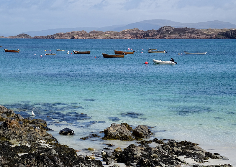 Small boats on the   turquoise blue waters of Iona © 2015 Scotiana